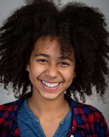 stock photo of wacky  - portrait of a beautiful mixed race girl with wacky afro hair style laughing in a checkered shirt isolated against a grey background - JPG