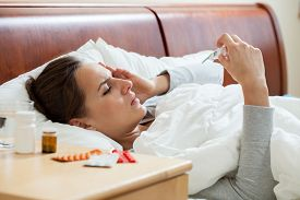 picture of high fever  - Image of having high fever woman holding thermometer - JPG