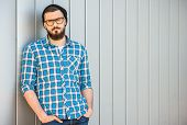 pic of beanie hat  - Young confident man with beard in glasses and hat is looking at the camera - JPG