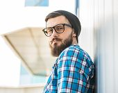 stock photo of beanie hat  - Young trendy man is standing outdoor in hat and glasses and looking at the camera - JPG