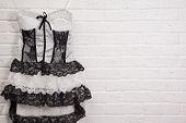 stock photo of underskirt  - Vintage white dress on a brick wall background - JPG