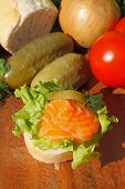 picture of baguette  - Slice of baguette with smoked salmon filet garnished with lettuce onion tomato and pickles on a wooden board - JPG