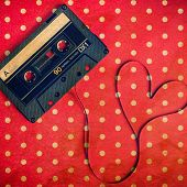 foto of magnetic tape  - audio cassette with magnetic tape in shape of heart on red dot polka background - JPG