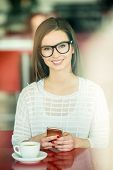 picture of pullovers  - Young smiling beautiful girl in glasses and white pullover sitting in urban cafe with a cup of coffee and holding smart phone - JPG