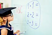 stock photo of little school girl  - Cute little student girl in academic hat during the lesson at school - JPG