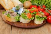 stock photo of baguette  - Baguette slices with herring salmon pollock and tuna garnished and topped with onions tomatoes pickles and salad - JPG