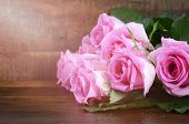pic of nurture  - Happy Mothers Day fresh pink roses on dark wood distressed table and background with applied retro vintage style filters and added lens flare sun stream - JPG