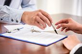 image of contract  - Young woman is signing financial contract with male realtor - JPG