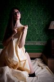 stock photo of sexuality  - Sexy brunette in bed on green vintage pattern wall - JPG
