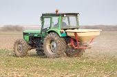 pic of fertilizer  - Tractor fertilizing farmland on cloudy day in springtime - JPG