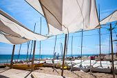 picture of sails  - Awnings in sails shape covering relax area near sailing boats on sandy beach in Calafell town coast of Mediterranean sea Catalonia Spain - JPG