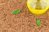 pic of flax seed oil  - Macro view of flax seeds and glass bottle of oil with leaves - JPG