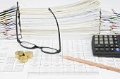 foto of spectacles  - Brown pencil with vertical spectacles and gold coins have pile of paperwork as background - JPG