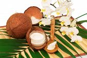 foto of coco  - Coconut cocos with cream wooden spoon white orchid and green palm leaves isolated on white background - JPG