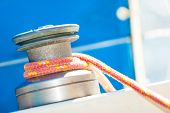 stock photo of yachts  - Winch capstan with rope on sailing boat. Yachting yacht in blue baltic sea sunny day summer vacation. Tourism luxury lifestyle.