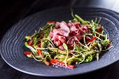 pic of bacon  - Authentic salad with bacon fresh red pepper sprouts sesame and olive oil on a black plate - JPG
