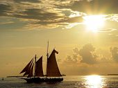 pic of u-boat  - full sail ship against an amber colored sunset on the ocean with the u.s. flag flying from the mast.