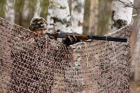 picture of hunter  - The hunter aims from behind camouflage netting - JPG