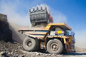 stock photo of mines  - Loading the gold ore into heavy dump truck at the opencast mining - JPG