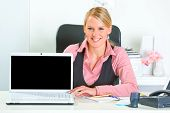 Smiling modern business woman sitting at office desk and showing laptop with blank screen
