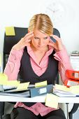 Tired modern business woman sitting at workplace overwhelmed with sticky reminder notes
