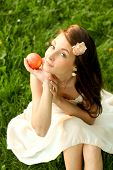 brunette young girl with an apple in summer park enjoying