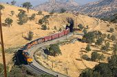 picture of bnsf  - Diesel electric locomotives drag their train up Tehachapi Mountain California - JPG