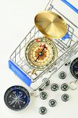 big golden compass in cart and ten black compasses isolated on white