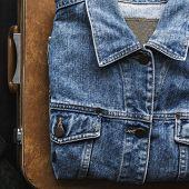 Denim jacket textile folding on luggage poster