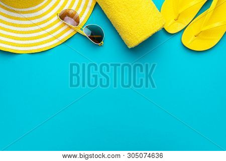 poster of Yellow Summer Beach Accessories On Turquoise Blue Background - Sunglasses, Towel. Flip-flops And Str