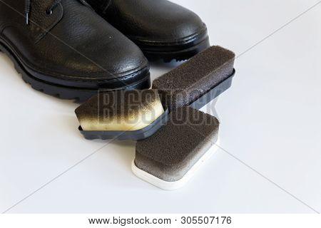 poster of Black Shoes And Shoe Sponge On White Background. Shoe Care With A Shoe Sponge. Shoe Sponge. No Peopl