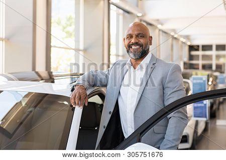 poster of African salesman standing in car showroom near opened door of luxury car. Happy businessman buying h