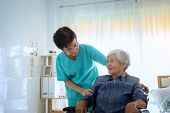 Delighted Positive Caregiver Helping Her Patient, Nurse Hugging His Senior Woman Patient Sitting On  poster