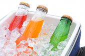 Closeup of three different soda bottles in a small cooler full of ice cubes.