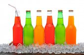 A line of assorted soda bottles standing in a field of ice cubes on a wooden table. Horizontal forma