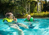 Senior couple splashing, playing, and having fun at a water park. Smiling and having a great vacatio poster