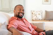 Portrait of happy mature african american man sitting on couch. Satisfied black man looking at camer poster