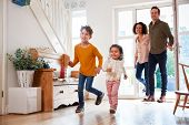 Family Returning Home After Trip Out With Excited Children Running Ahead poster