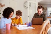 Father Works On Laptop As Mother Helps Son With Homework On Kitchen Table poster