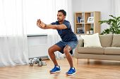 sport and healthy lifestyle concept - indian man with fitness tracker exercising and doing squats at poster