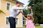 Family affairs - father and daughter playing in summer; he is dancing with her in the garden in fron