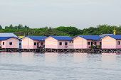 Wooden Pink Houses In Floating Villages In Labuan Pearl Of Borneo,malaysia.houses Community Standing poster
