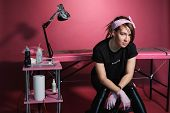Portrait Of A Professional Tattoo Master Woman. Black Clothes, And Dreadlocks. Red, Pink And White B poster
