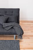 stock photo of futon  - Gray sofa with cushions and throw - JPG
