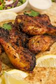 image of raita  - Tandoori chicken legs served on top of a naan bread, with salad, raita and lemon wedges.