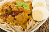 picture of ayam  - Dry Curry Mee - Malaysian chicken curry with coconut milk and noodles served with boiled egg on a woven mat.