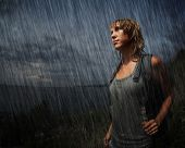 Woman with backpack and wet face, hair and wet closing standing in the midst of darkness. Artificial rain added