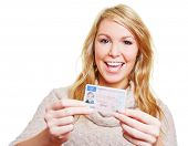 Happy young woman showing proudly her new driving licence
