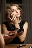Blonde woman doing evening make-up before mirror