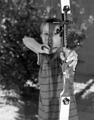 stock photo of fletching  - Focus on Target Sight - Close up of a young boy drawing back a bow and arrow